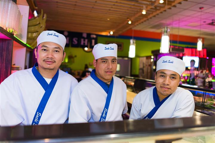 "three chefs, wearing uniforms and hats that read, ""Sachi Sushi"""