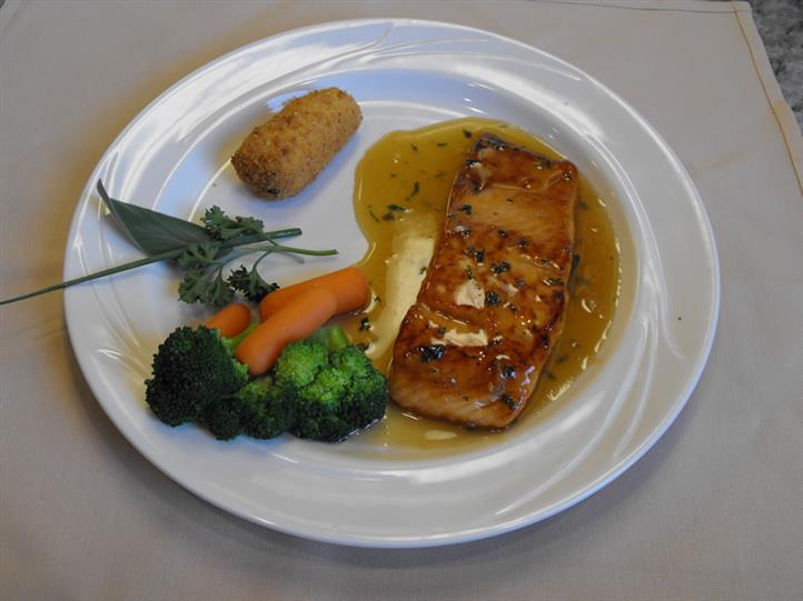 salmons with sauce and side of carrots and broccoli