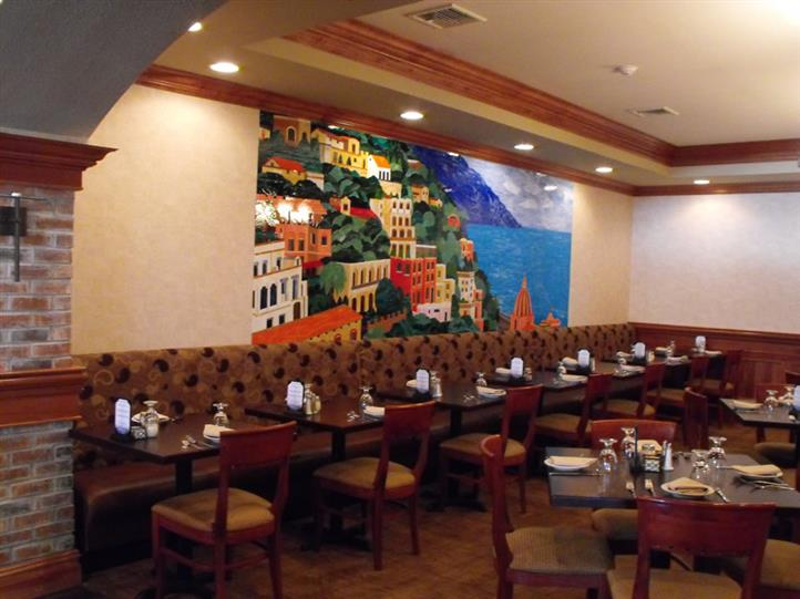 dining area, with a mural of an Italian seaside village