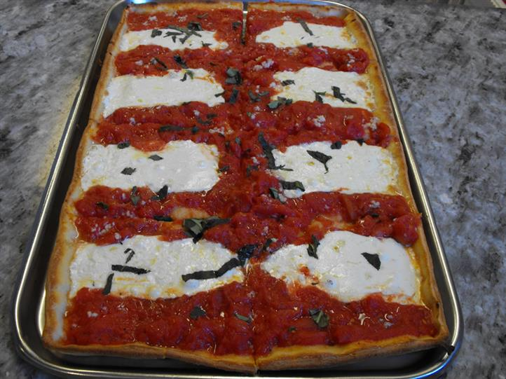rectangular pizza slice with sauce, basil and mozarella