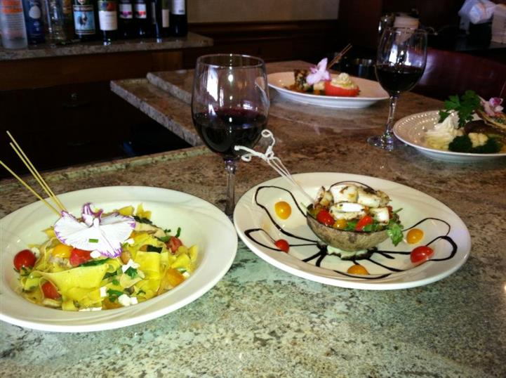 two different salad dishes, with a glass of red wine