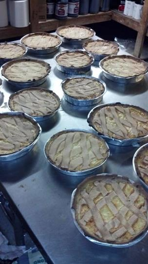 a table with over a dozen uncooked pies