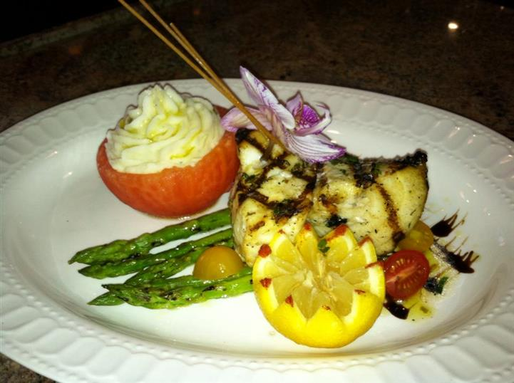 grilled chicken served over asparagus with vegetables and fruit