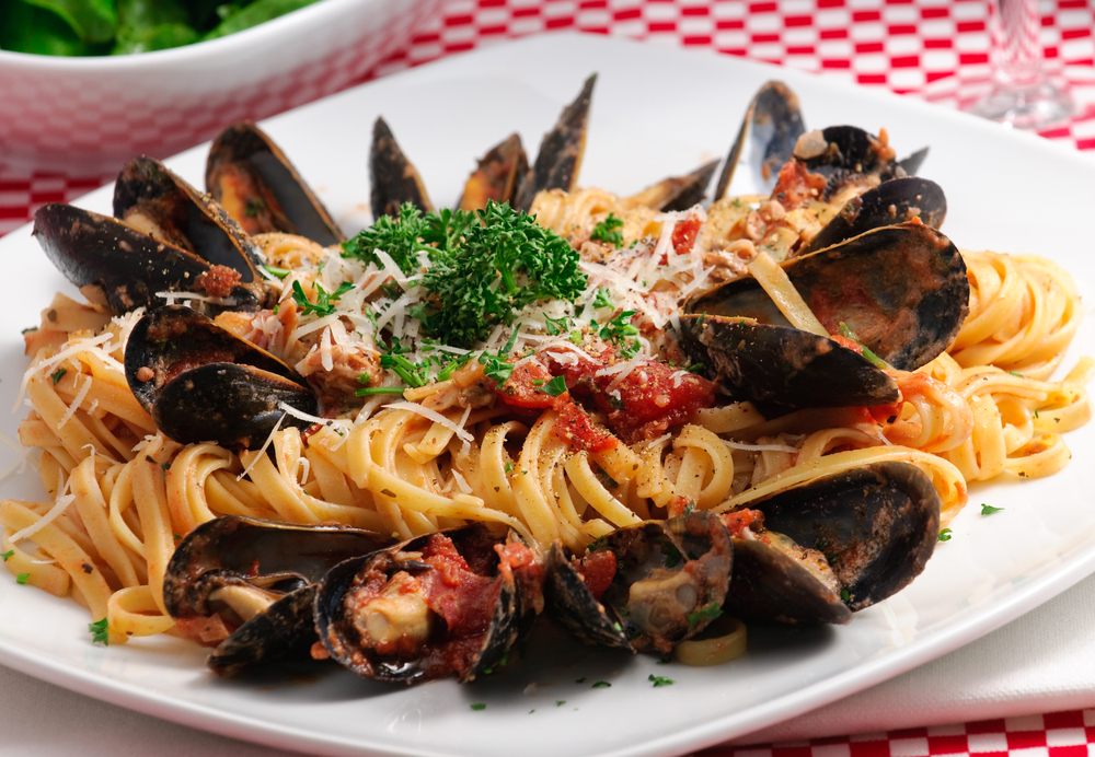 A bowl of spaghetti with mussels, tomato sauce, garnish and a sprinkle of cheese