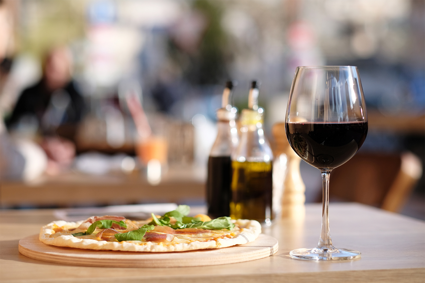 A glass of red wine on a table with a small pizza on a wooden board