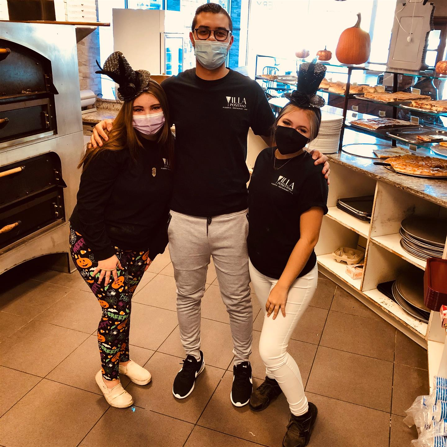 Three restaurant workers with halloween costumes