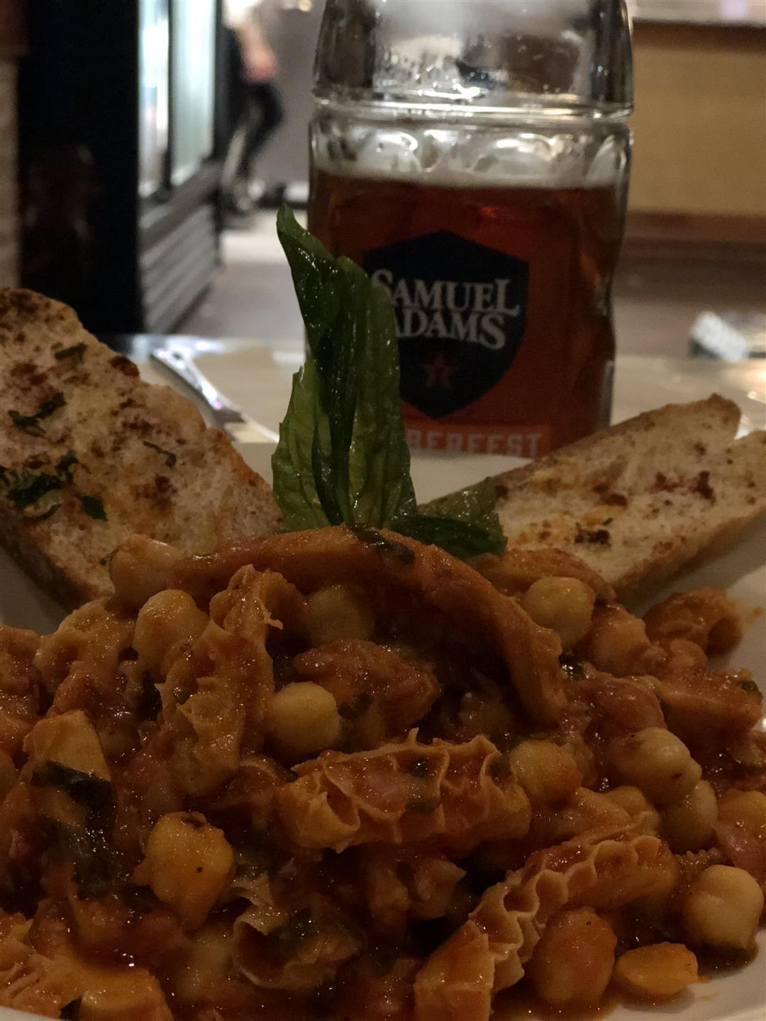 menu item with chickpeas and lettuce with two slices of italian bread seasoned and a pint of sam adams next to it