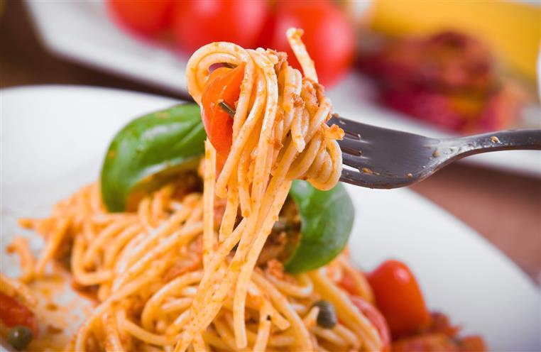 Spaghetti on a fork with cherry tomatoes and basil