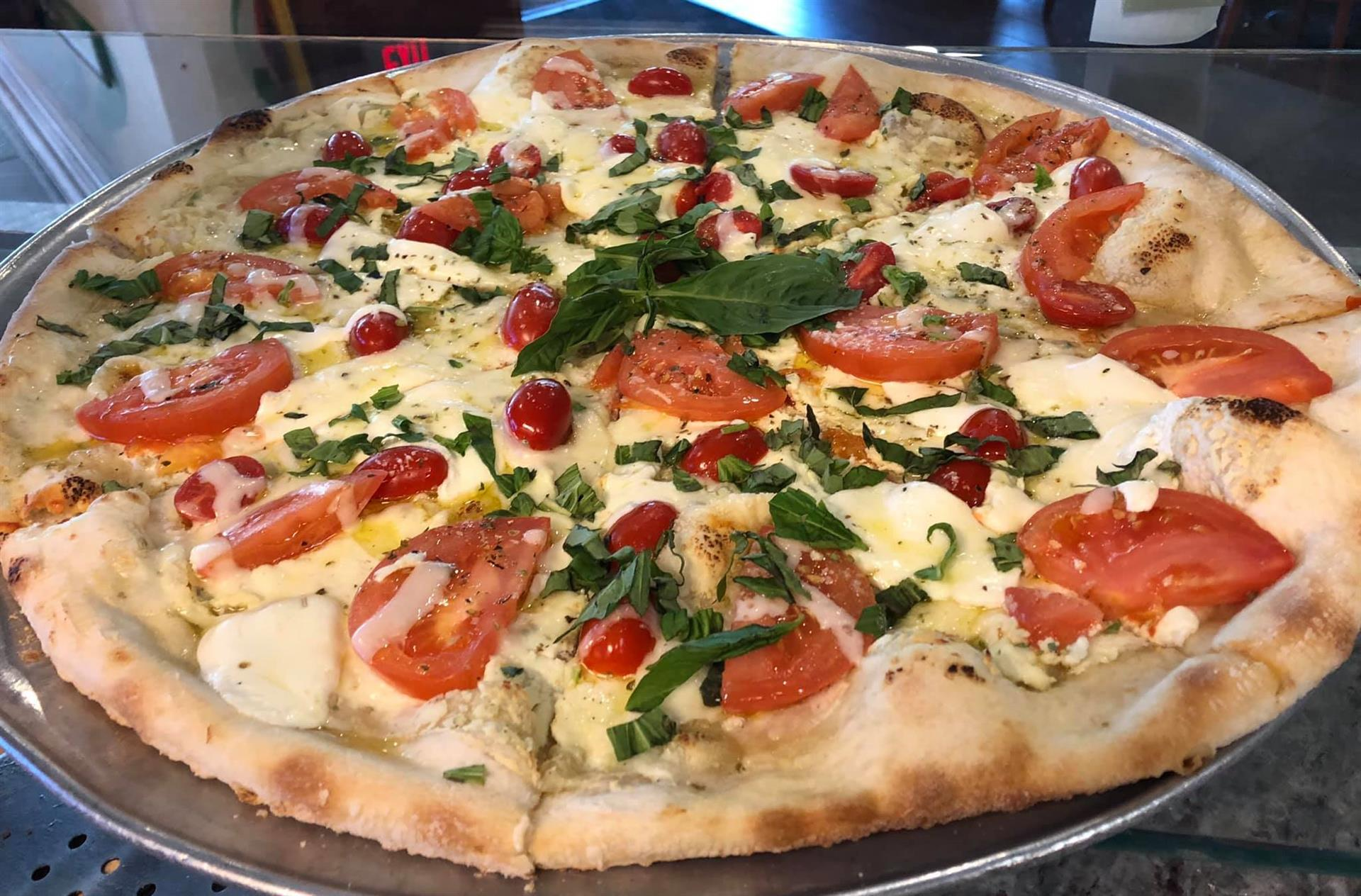 cheese pizza topped with tomatoes and spinach