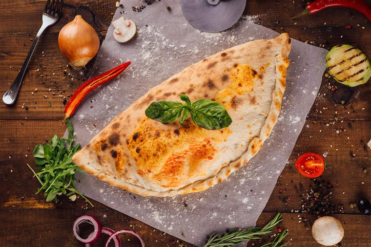 Pizza calzone on a dark wooden brown background with vegetables, herbs and spices