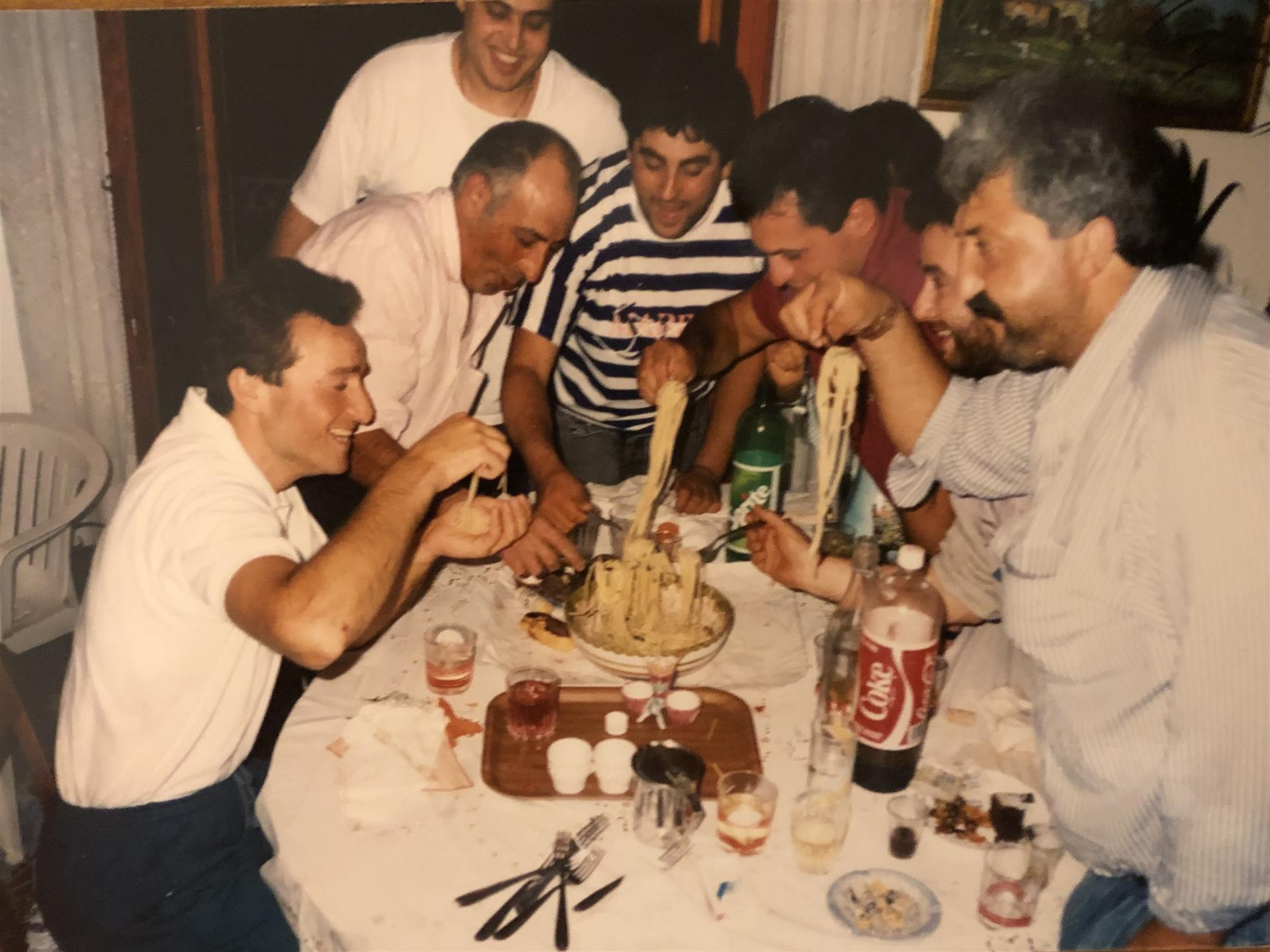 family gathering around a table earting pasta