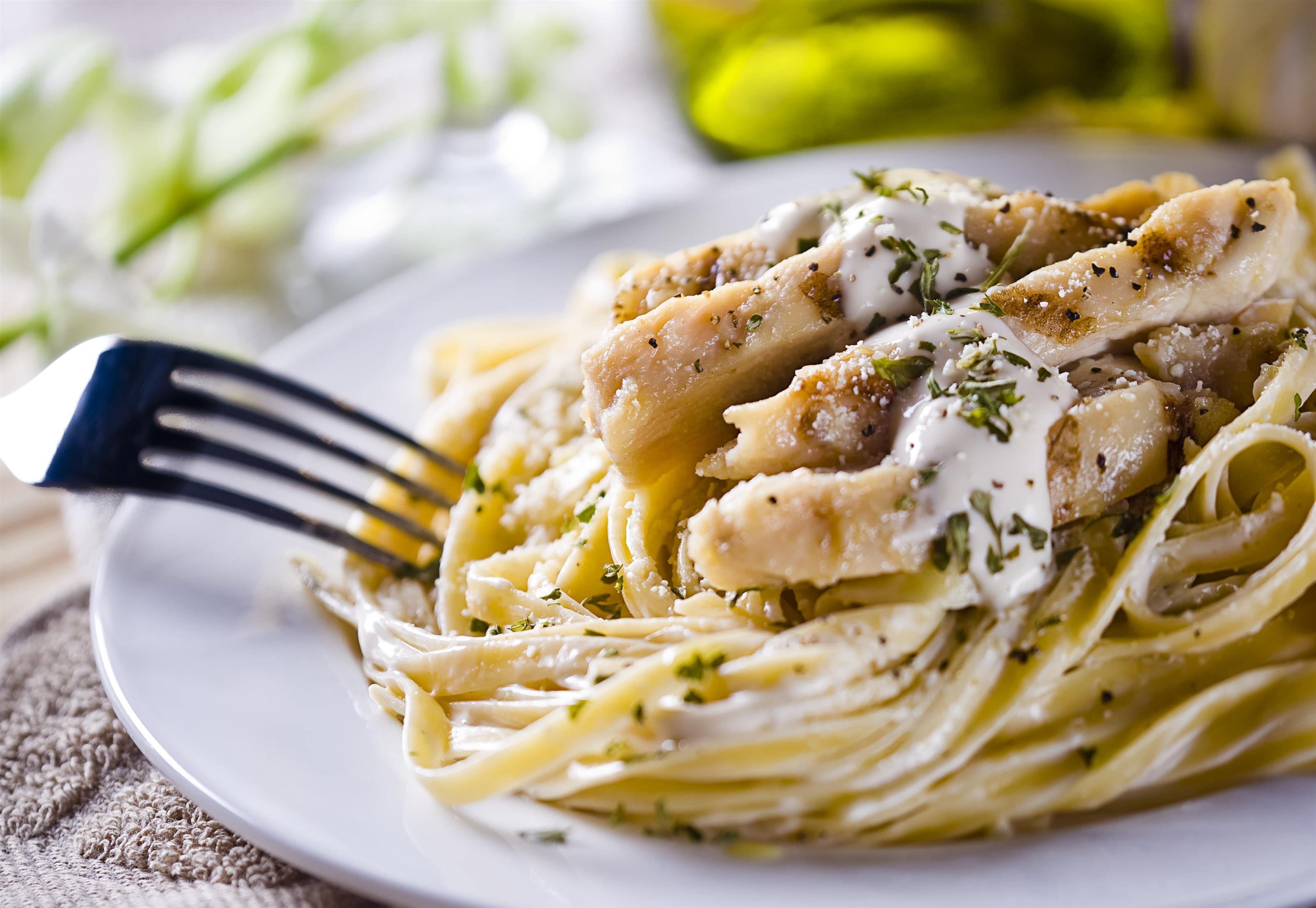 Linguine alfredo with grilled chicken on white dish with fork