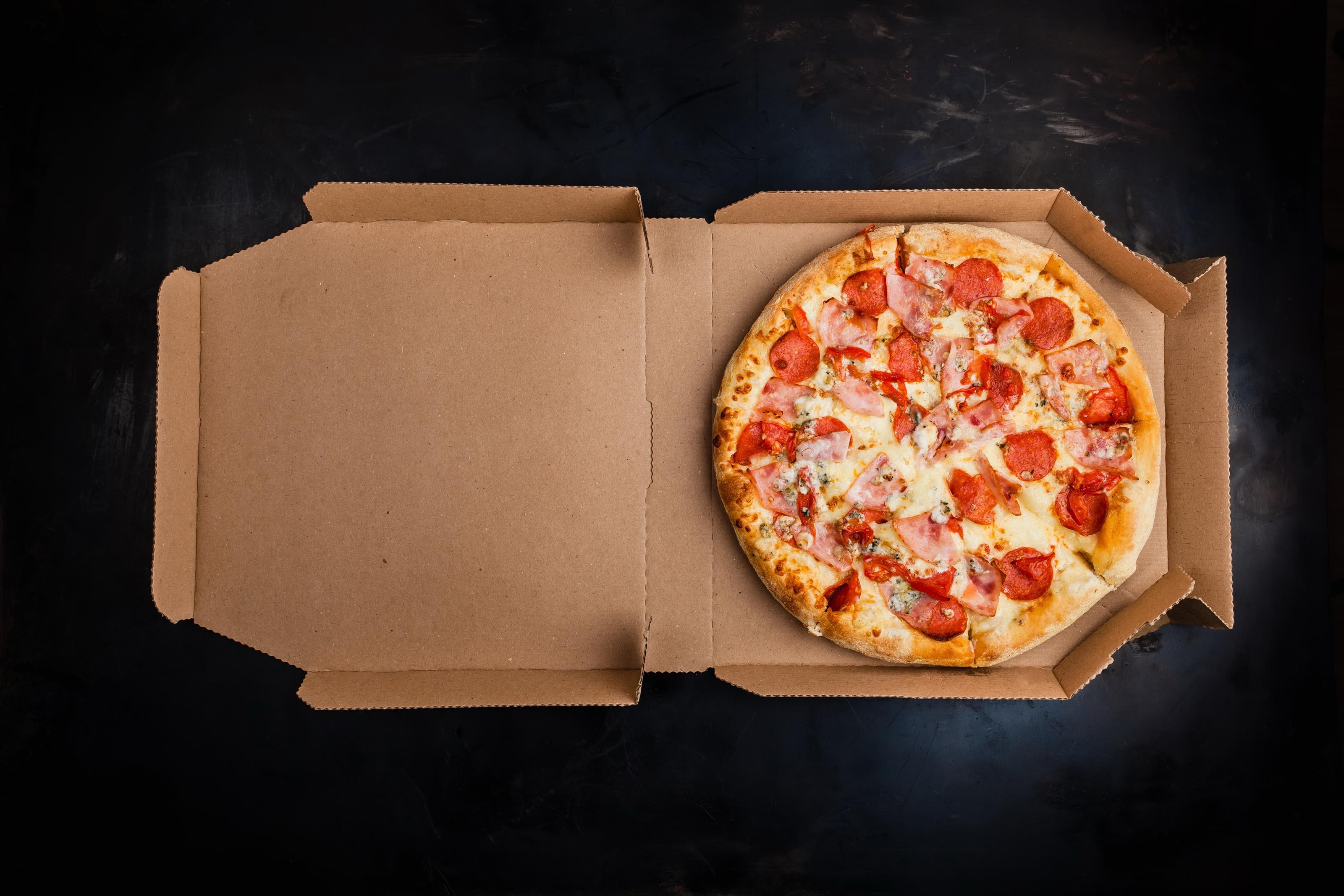 Whole pizza pie with pepperoni and ham in open pizza box on slate table