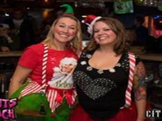 Two women dressed in Christmas outfits posing for picture