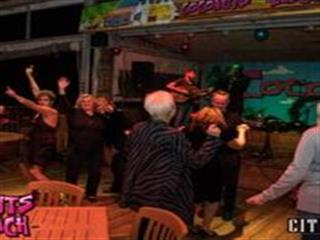 People dancing in bar in front of band on stage