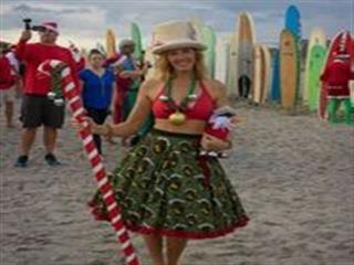 Woman in holiday skirt and holding large candy cane poses for photo
