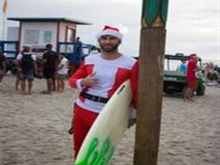 Man in santa costume and holding surfboard poses for photo