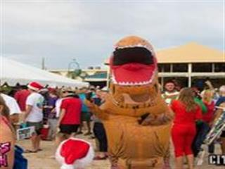 Person in dinosaur costume on crowded beach