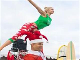 Man in santa suit lifting female gymnast over head