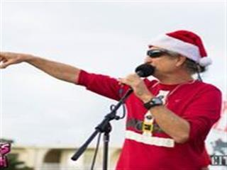 Man in christmas outfit speaking in to microphone on stage