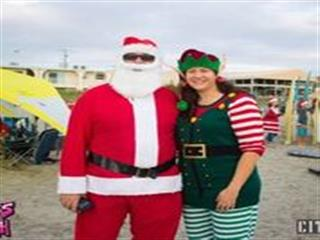 Man and woman in santa and elf costumes posing for photo