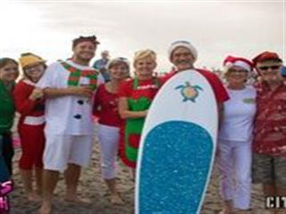 People in christmas outfits standing behind surfboard at beach