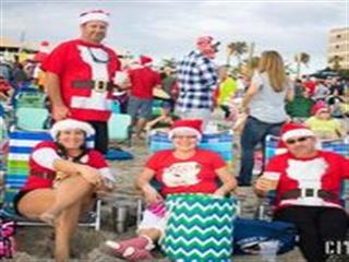 People dressed in christmas outfits sitting in beach chairs