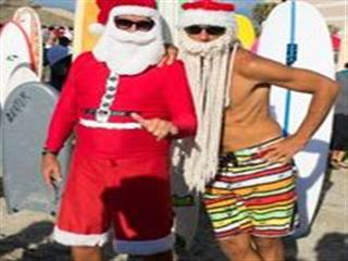 Men in santa outfits and beards posing for photo on beach