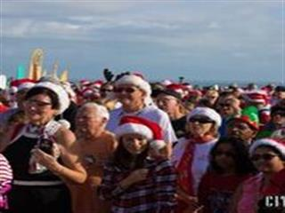Crowd of spectators at beach wearing christmas clothes