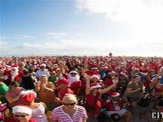 Crowd of people dressed in santa outfits at beach