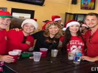 Women in santa hats standing at table posing for photo