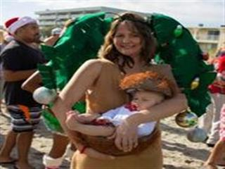 Woman dressed as palm tree holding baby in coconut basket