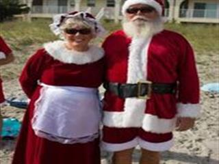 Santa and Mrs Claus on beach posing for photo