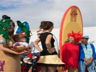 Men and women in christmas holiday costumes on beach