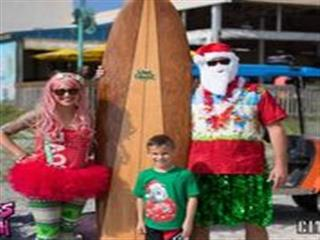Young boy in front of surfboard with elf and Santa posing for picture