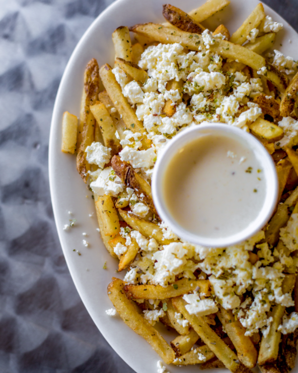French Fries with crumbled Feta and cup of tzatziki on plate.