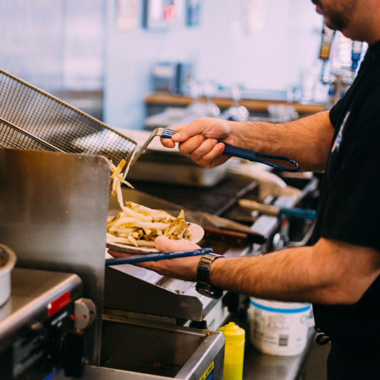 Cook removing french fries from the frier and plating them.