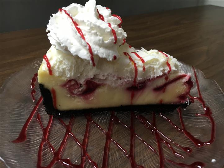 a raspberry cheesecake with whipped cream on top