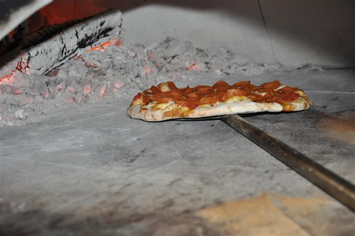Pepperoni pizza pie being put in the oven