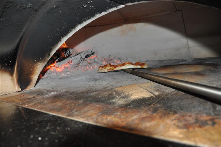 Pizza being  put inside of a oven