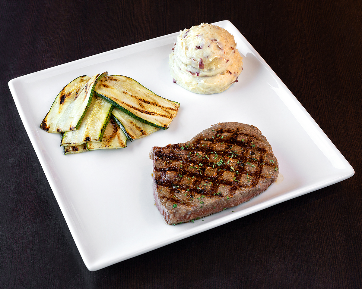 Sirloin served with mashed potatoes and grilled zucchini