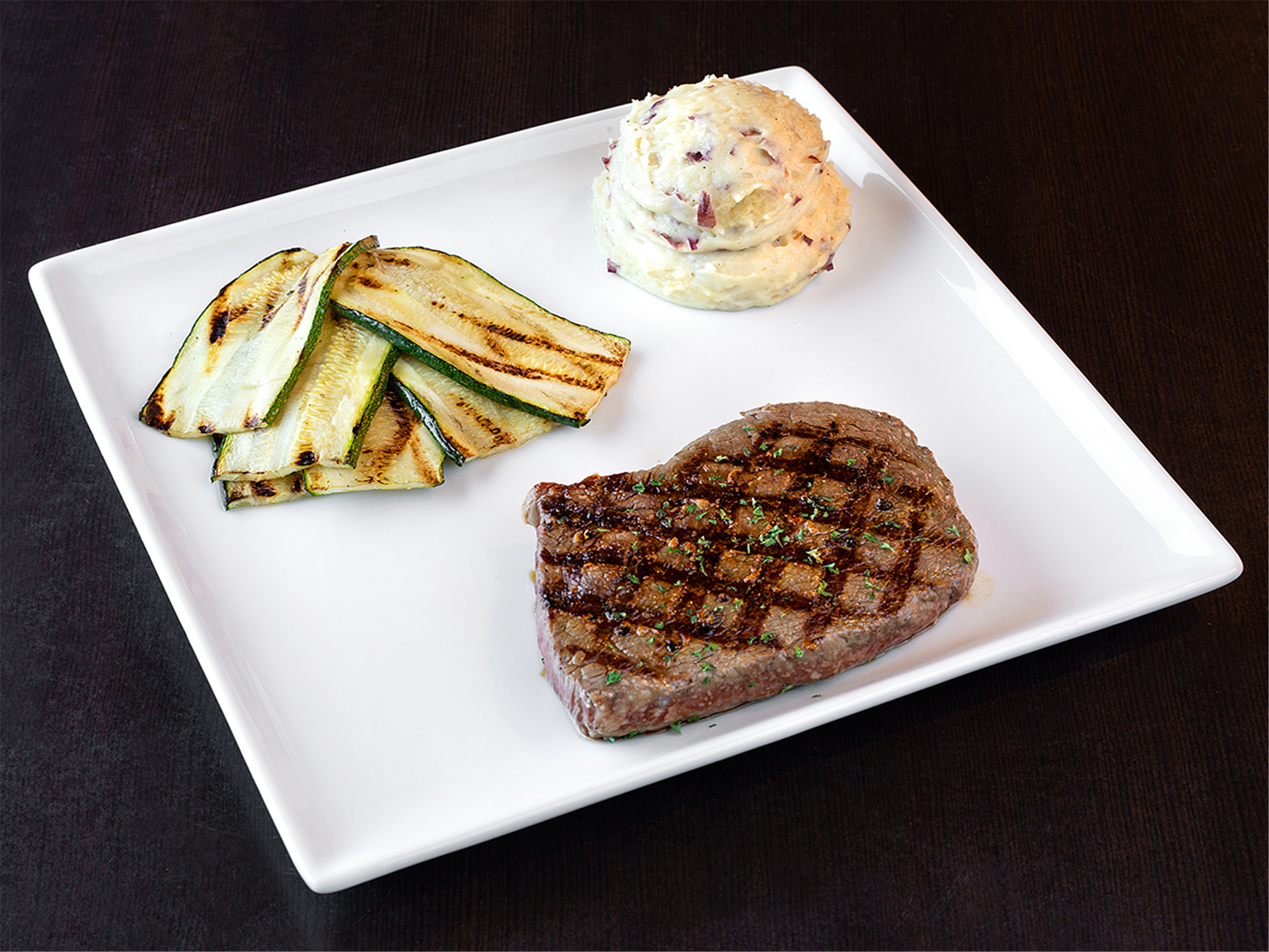Sirloin with a side of mashed potatoes and grilled zuchinni