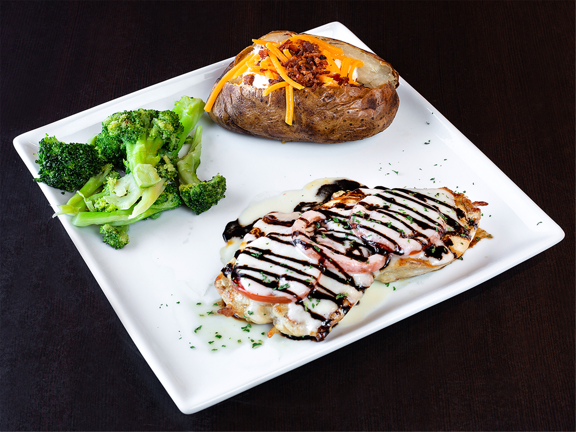 Chicken Balsa wood-fired chicken breast topped with roma tomatoes, lemon wine sauce and a balsamic reduction.