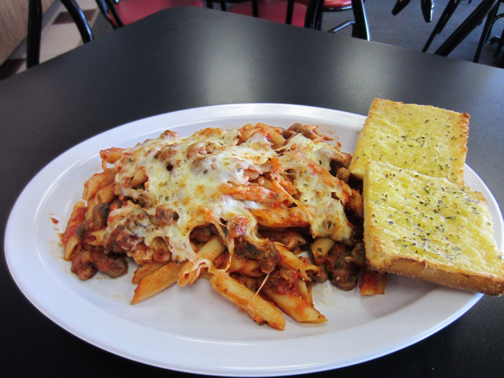 Baked ziti with garlic bread on a plate