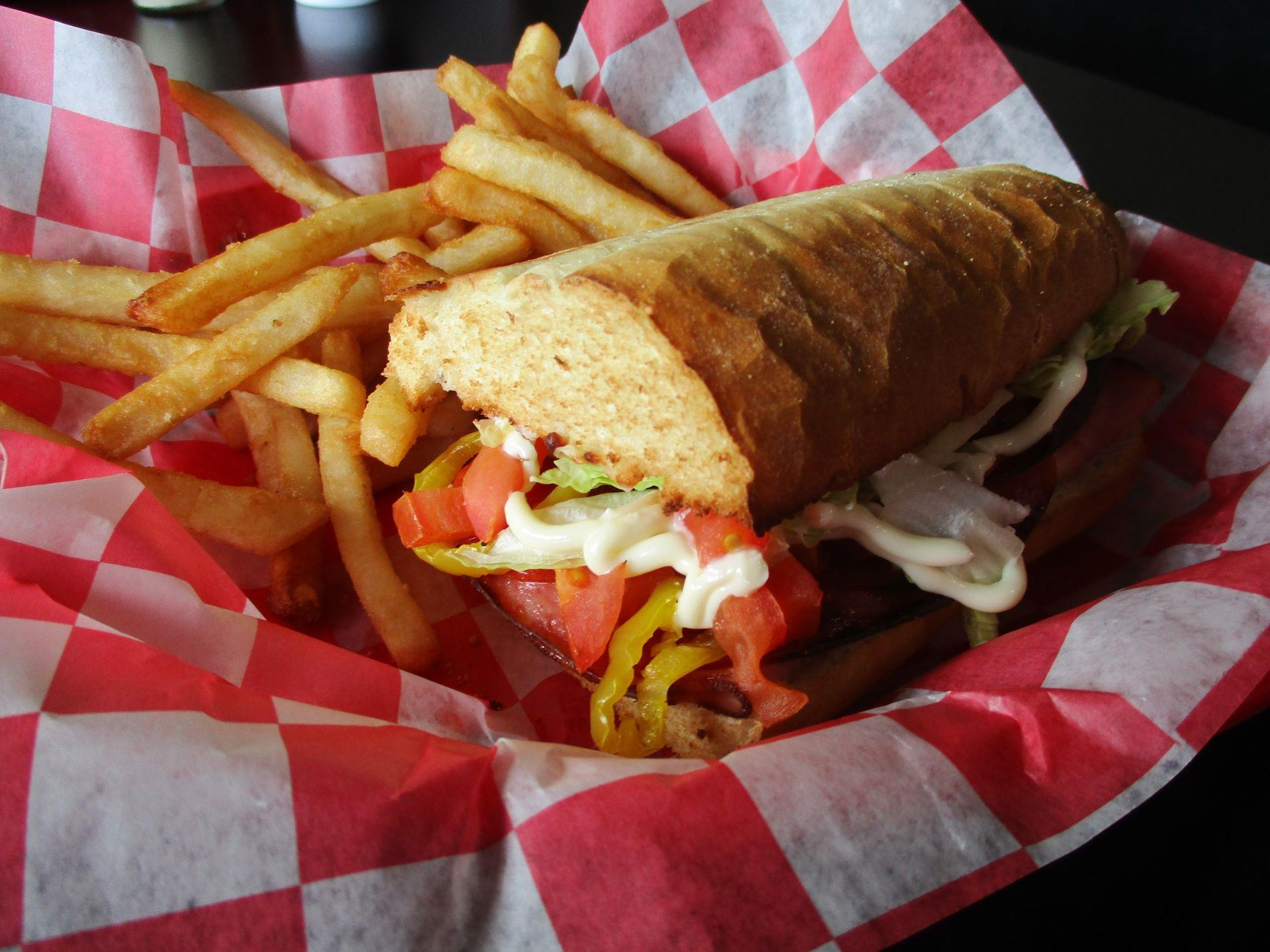 Toasted Italian sub in a basket with fries
