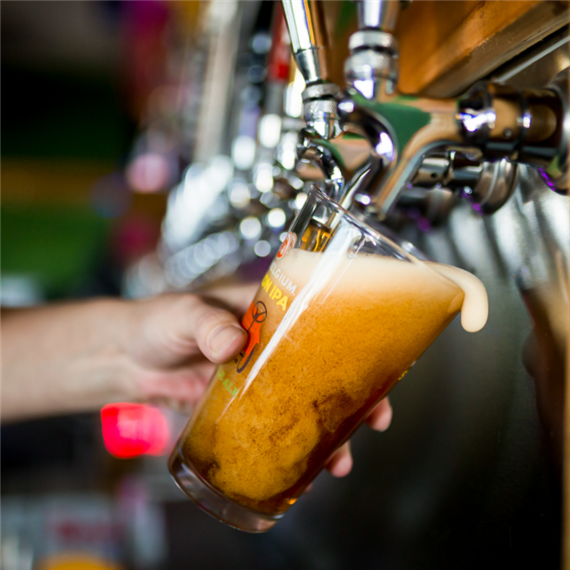 pint of beer being poured from tap into a glass