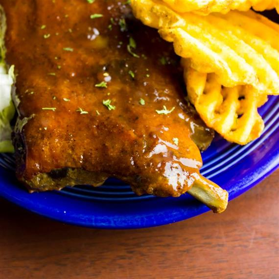 ribs on a plate with a side of waffle fries