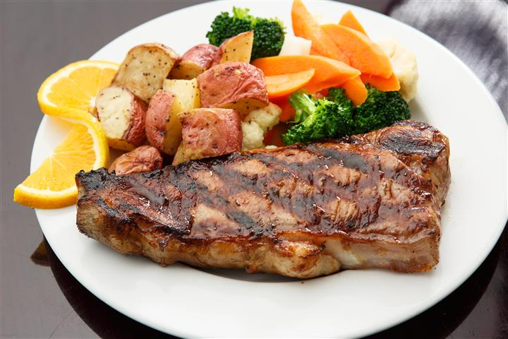 Grilled steak on a plate with potatoes, Broccoli, and carrots