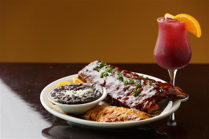 Ribs and black beans on a plate with a beverage with a orange garnish