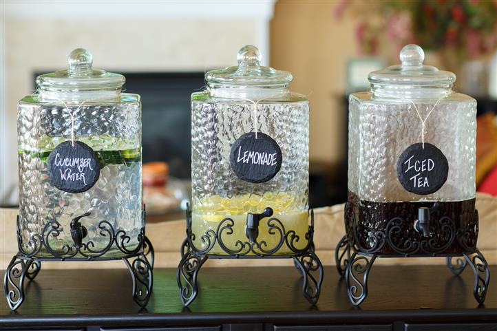 Cucumber water, Lemonade, and iced tea in decorative glass dispensers